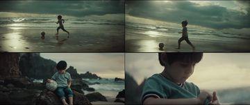 在海边踢足球的小男孩