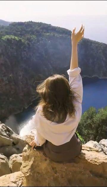 在海边悬崖上撩头发的女孩