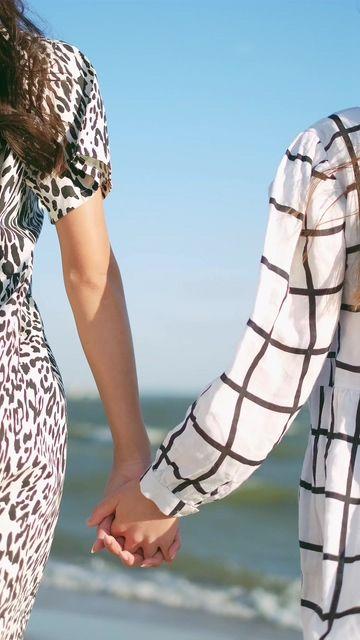 在海边两个牵手的女孩竖屏视频